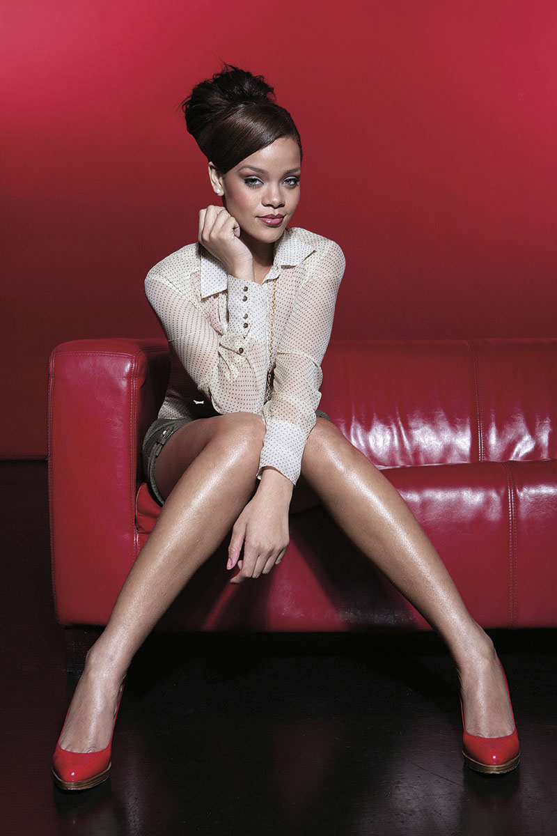 rihanna sitting on a red sofa